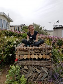 Photograph of our work experience candidate Laura, sitting on a bug hotel