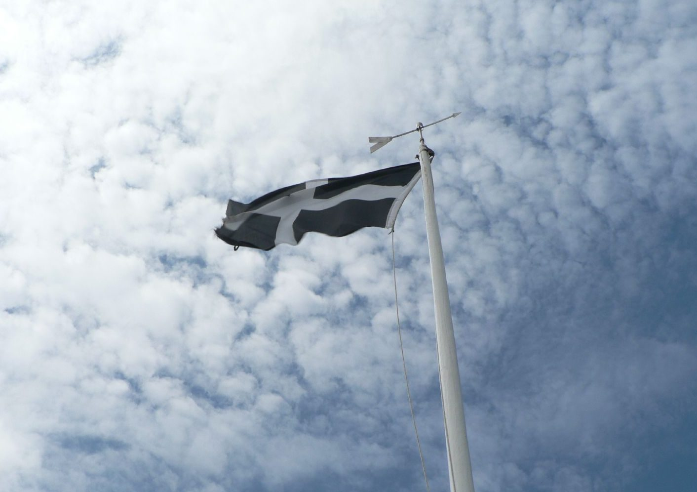 A picture of the cornish flag flying against the blue sky.